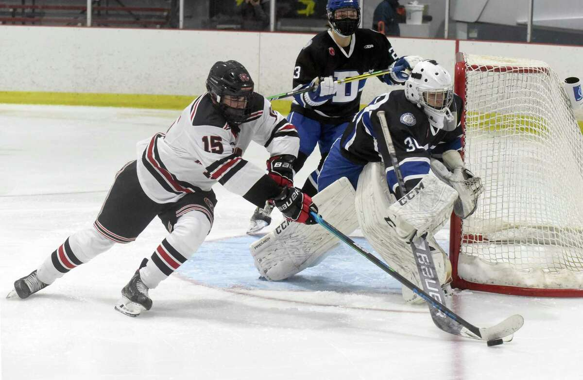 New Canaan's Doster Crowell (15) and Darien goalie Teddy DeBeradinis play the puck during a boys ice hockey game at the Darien Ice House on Wednesday, Feb. 17, 2021.