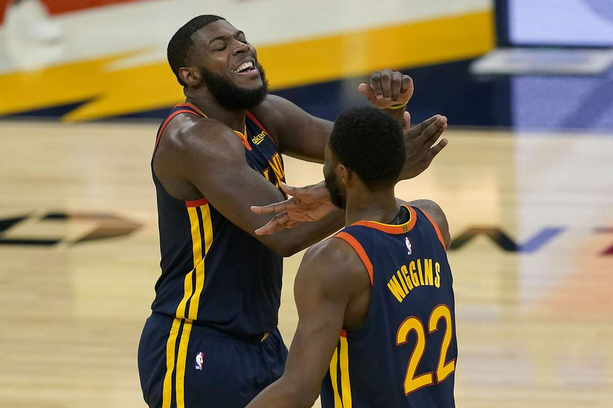 Golden State Warriors forward Eric Paschall, left, celebrates with forward Andrew Wiggins (22) during overtime of the team's NBA basketball game against the Miami Heat in San Francisco, Wednesday, Feb. 17, 2021. (AP Photo/Jeff Chiu)