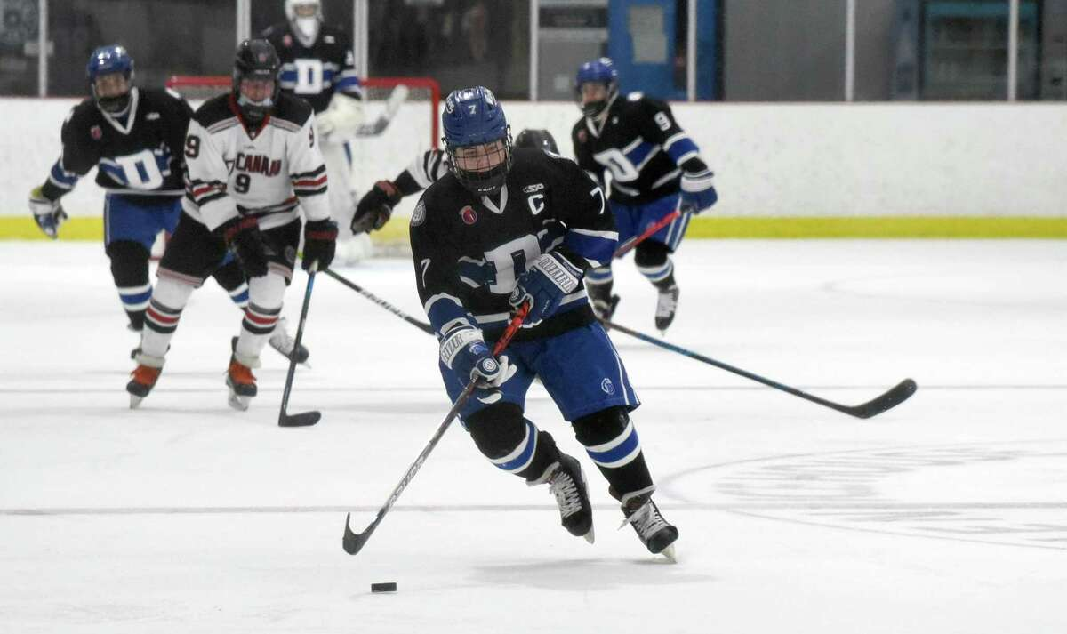 Darien's Sam Erickson (7) skates with the puck during the Blue Wave's boys ice hockey game against New Canaan at the Darien Ice House on Wednesday, Feb. 17. 2021.