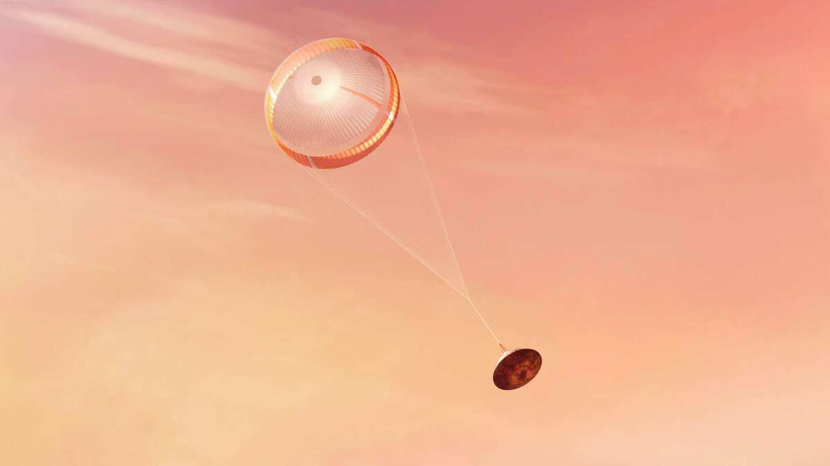 In this illustration made available by NASA, the Perseverance rover deploys a supersonic parachute from its aeroshell as it slows down before landing on the surface of Mars. (NASA/JPL-Caltech via AP)