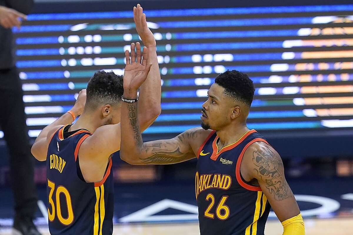 Golden State Warriors guard Stephen Curry, left, celebrates with forward Kent Bazemore during the second half of the team's NBA basketball game against the Miami Heat in San Francisco, Wednesday, Feb. 17, 2021. (AP Photo/Jeff Chiu)