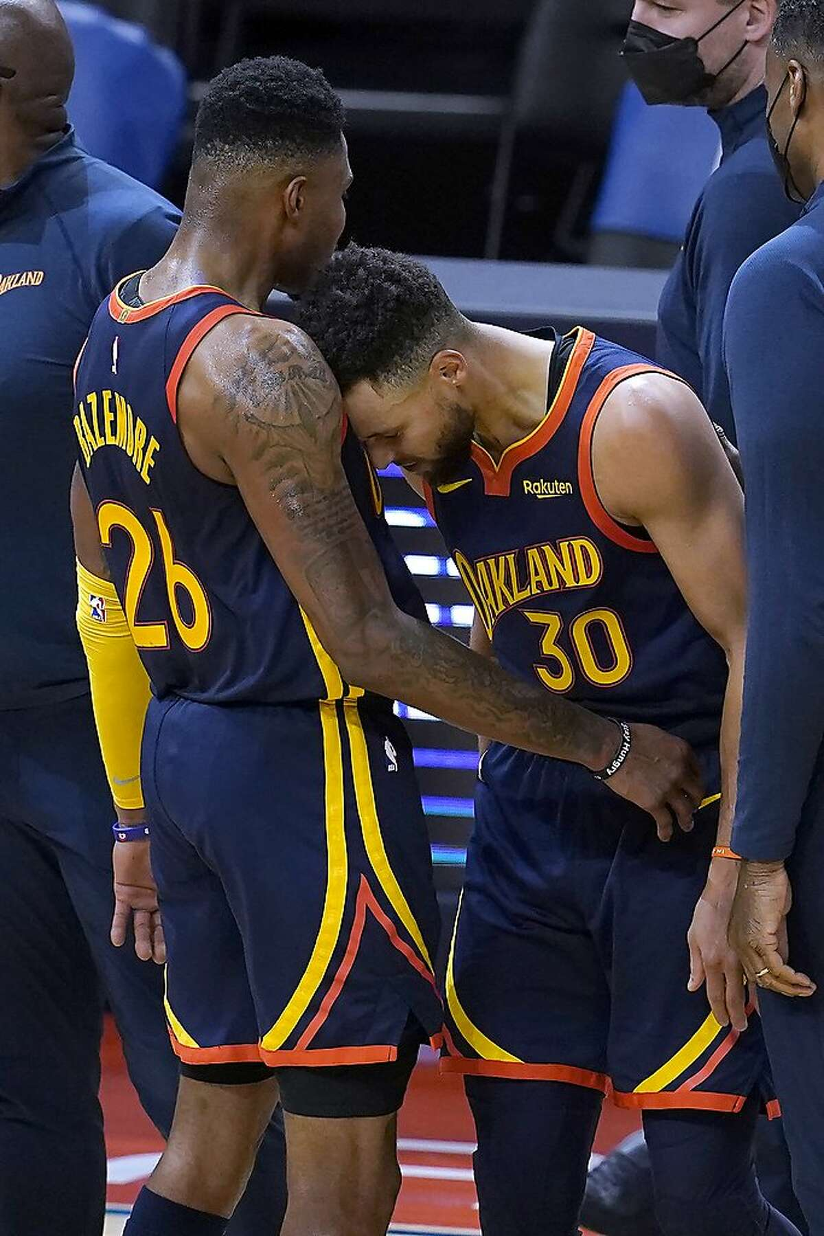Golden State Warriors forward Kent Bazemore (26) celebrates with guard Stephen Curry (30) during overtime of the team's NBA basketball game against the Miami Heat in San Francisco, Wednesday, Feb. 17, 2021. (AP Photo/Jeff Chiu)