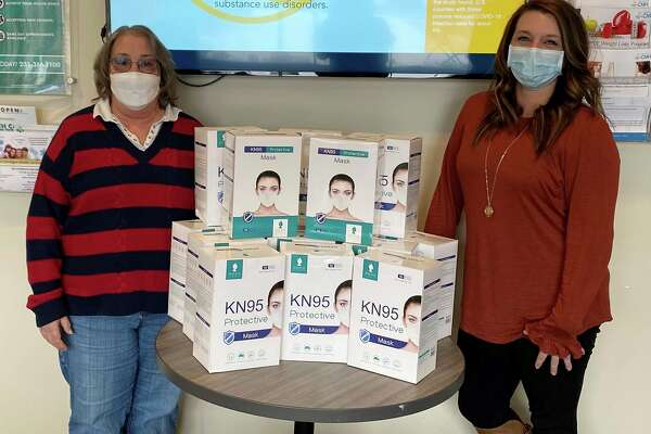 Michigan Department of Health and Human Services recently distributed 8,400 KN95 protective masks to 32 residential group home providers in Mason, Lake and Oceana counties as part of its the Mask Up, Mask Right campaign. West Michigan CMH assisted MDHHS with the local distribution. Pictured is Deb Davis (left), manager of the Samaratis group home in Scottville, accepting the masks from Nicole Kusebuski, network and QI specialist at West Michigan CMH. (Courtesy photo/Michigan CMH)