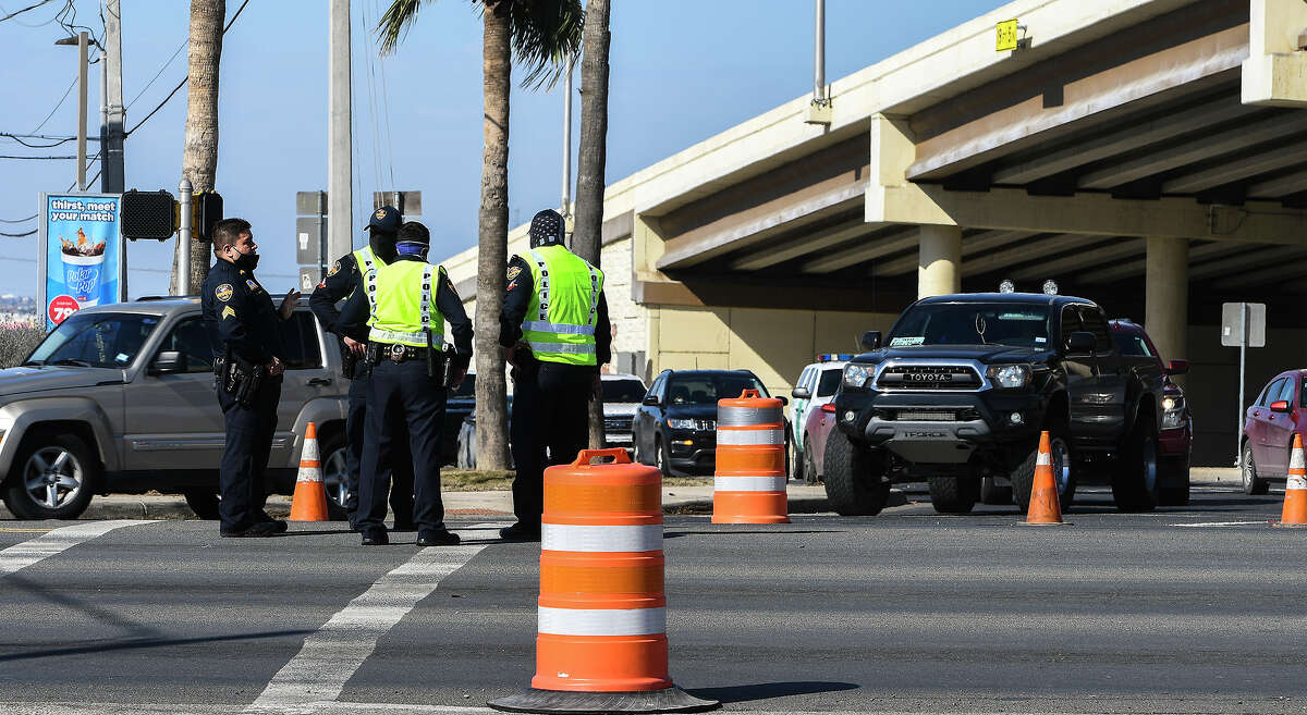 Laredo Police officers monitor the intersection of Bob Bullock Loop and Highway 359, Wednesday, Feb. 17, 2021, as Laredo continues to experience a black out throughout parts of the city.