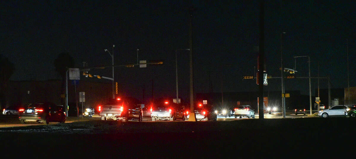 Motorists navigate through the Arkansas Avenue and East Saunders Street intersection during a black out affecting multiple parts of Laredo, Monday, Feb. 15, 2021, as Laredo experiences freezing temperatures following a winter storm.