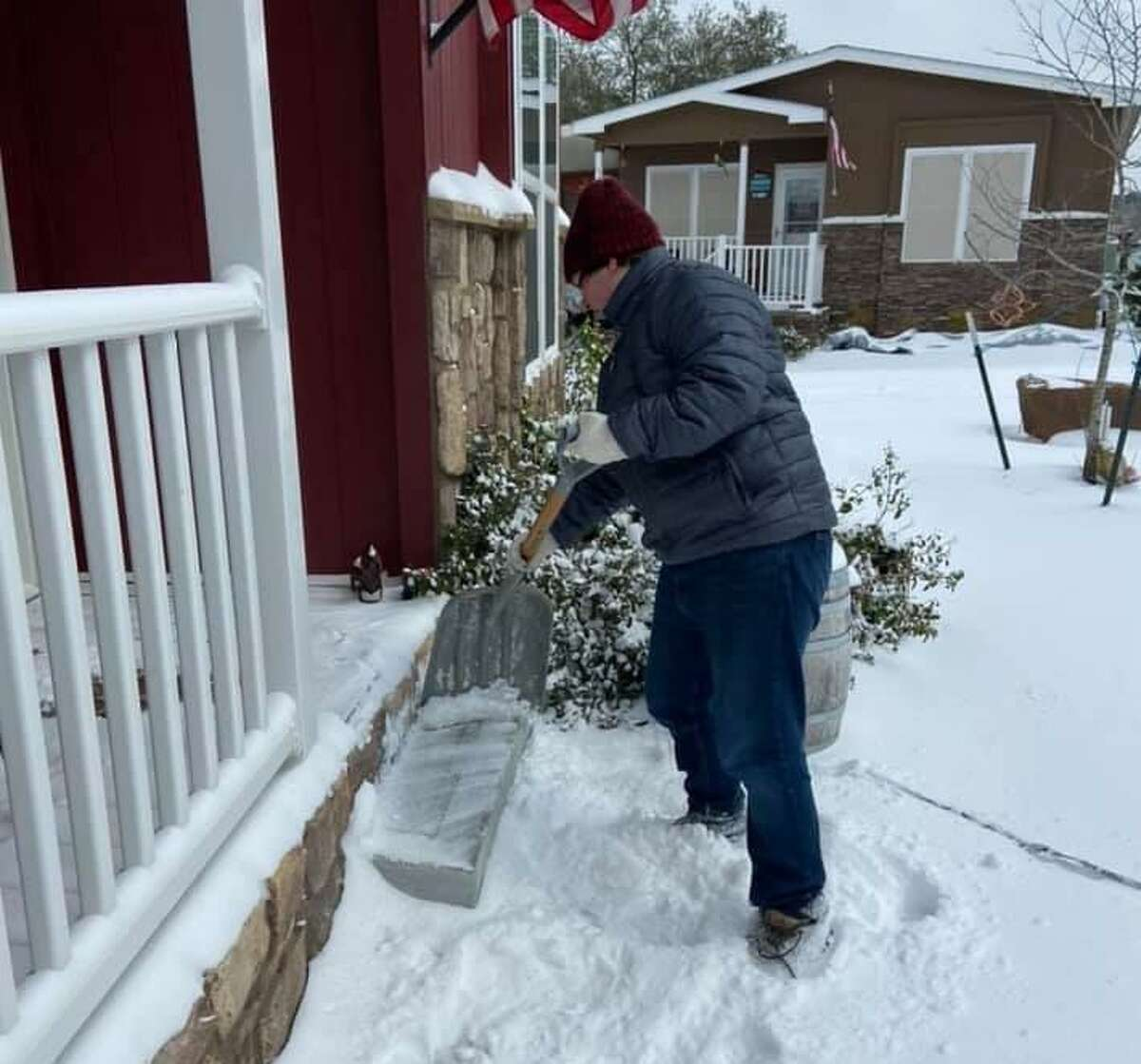 Ben Lake, 17, clears snow off of Jeff and Margie Taylor's porch and steps on Monday. Acts of kindness sprung up around the county as neighbors, friends and even strangers banded together to get through the winter storm that gripped the area.