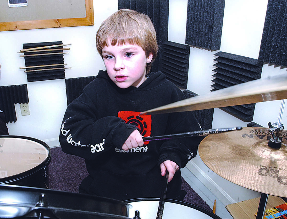 Benjamin Barrett, age 8, of Portland, is focused on his drumming during his one on one practice with Jon Peckman, of Wallingford, at Connecticut Valley School of Music in Portland Tuesday evening......photo by Sarah Schultz......2.22.05