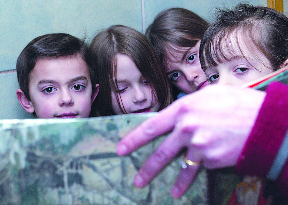 Christian Alberico, Lena Hunington, Lauren Davis, and Kristina Pascarelli, all second graders at Brewster Elementary School, listen intently as Diana Huntington reads them a story during First Friday Family Reading in Durham......photo by Sarah Schultz......2.4.05