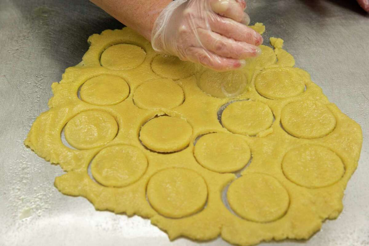 """Laykie Donin uses a wine class to cut circles out of a dough while demonstrating how to make traditional Hamentashen for the Jewish holiday of Purim Wednesday, Feb. 17, 2021, at Evelyn Rubenstein JCC Houston in Houston. Donin is the owner and chef the cafe at the JCC, """"Café at the J."""""""