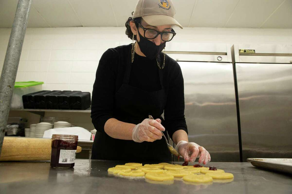 """Laykie Donin adds strawberry jam onto the dough while demonstrating how to make traditional Hamentashen for the Jewish holiday of Purim Wednesday, Feb. 17, 2021, at Evelyn Rubenstein JCC Houston in Houston. Donin is the owner and chef the cafe at the JCC, """"Café at the J."""""""