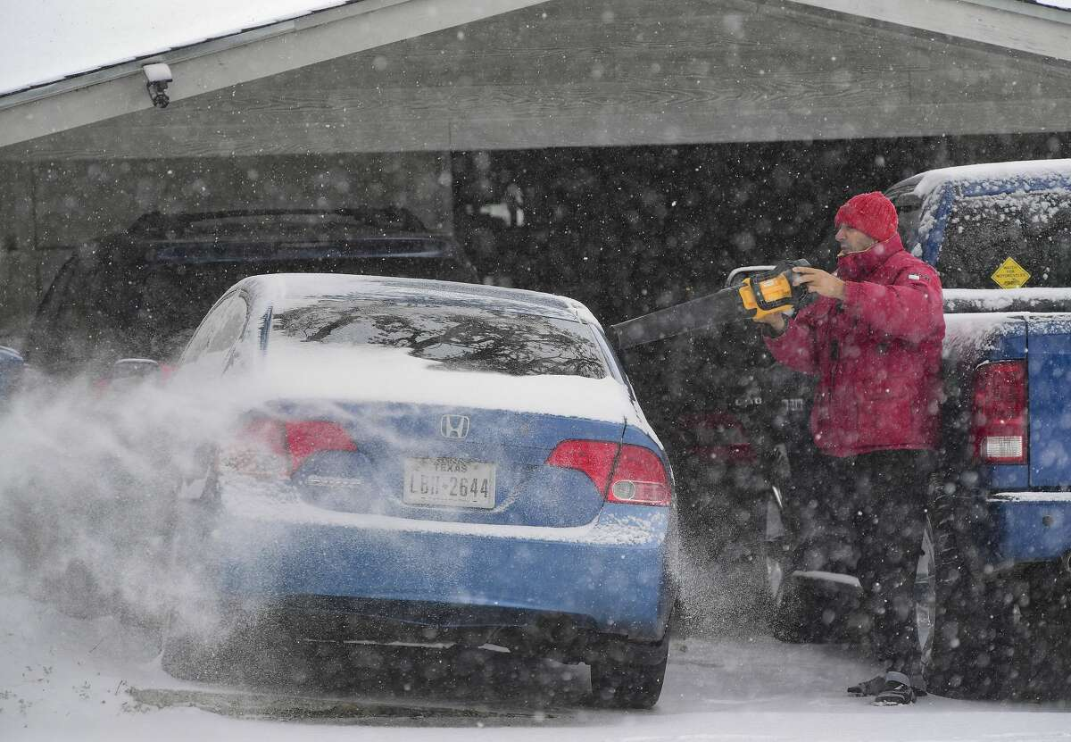 Saul Cortez uses a leaf blower to remove snow from his car on Thursday morning, Feb. 18, 2021.