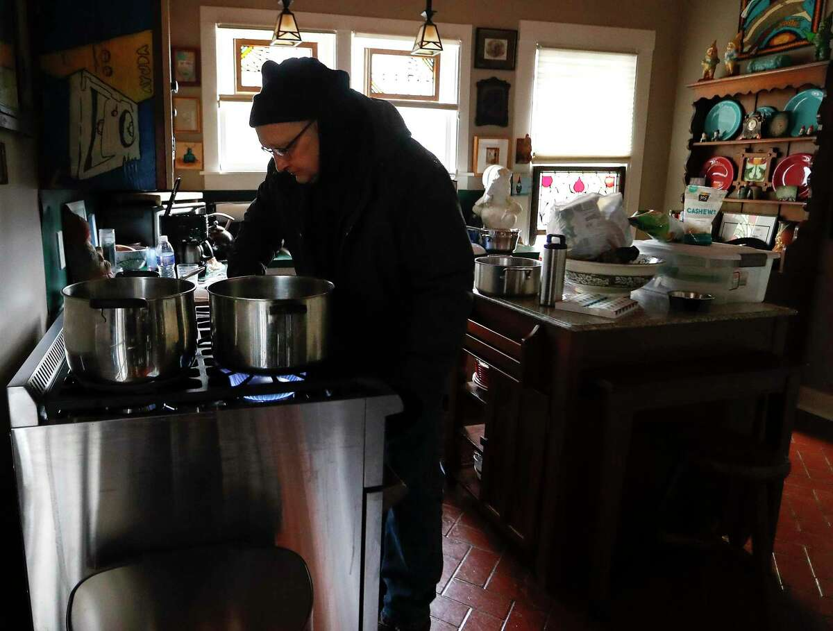 Heights resident Bill Weinle boils water on his stove to add heat in his home, which was without power and water, in Houston, Wednesday, February 17, 2021, after a winter storm left people without power and water along with freezing temperatures. The city announced it would deliver 10 trucks of potable water to Houston senior facilities Thursday.