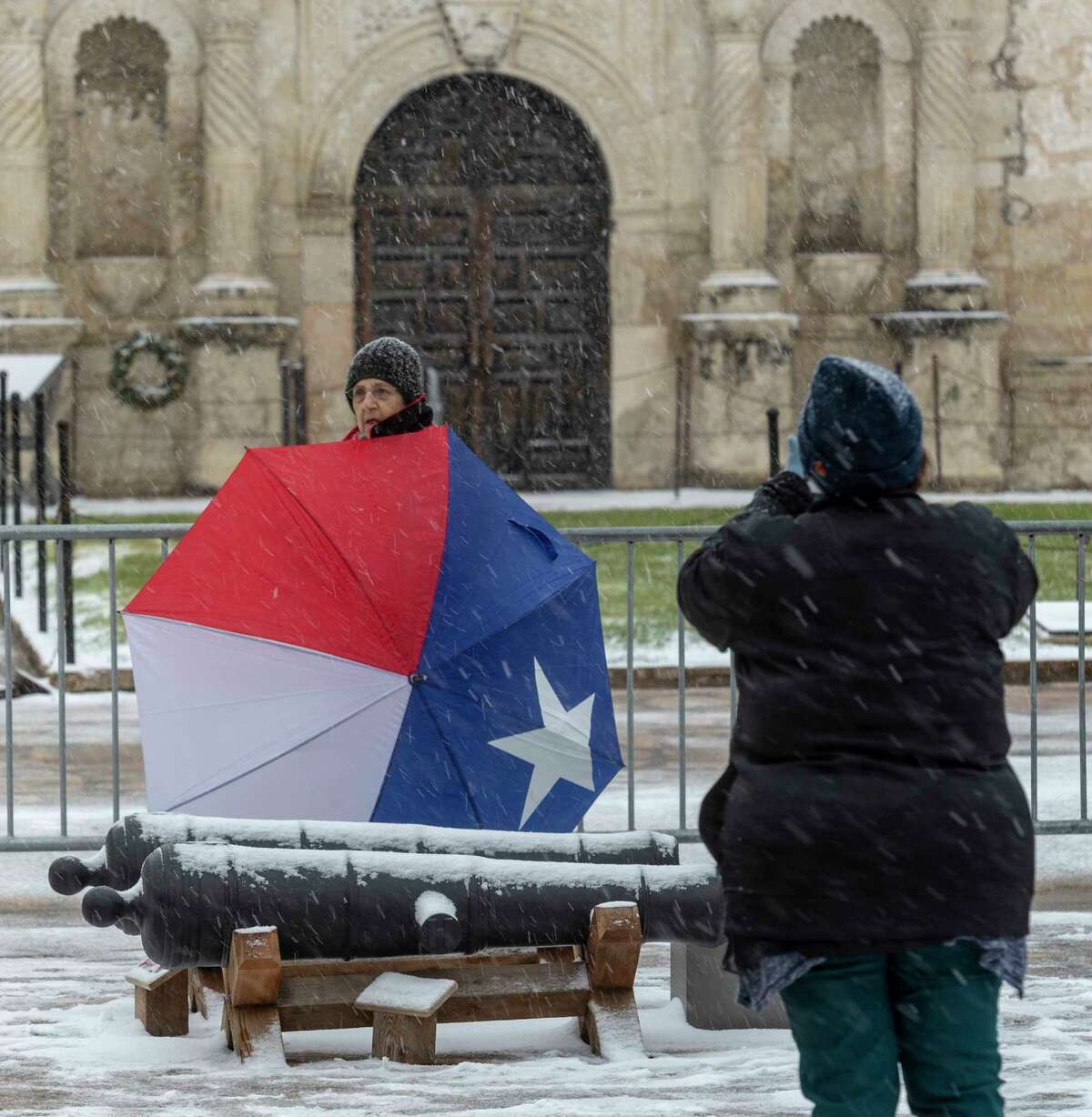Ruth Madorsky takes a picture Thursday, Feb. 18, 2021, in front of the Alamo as snow returns to San Antonio.