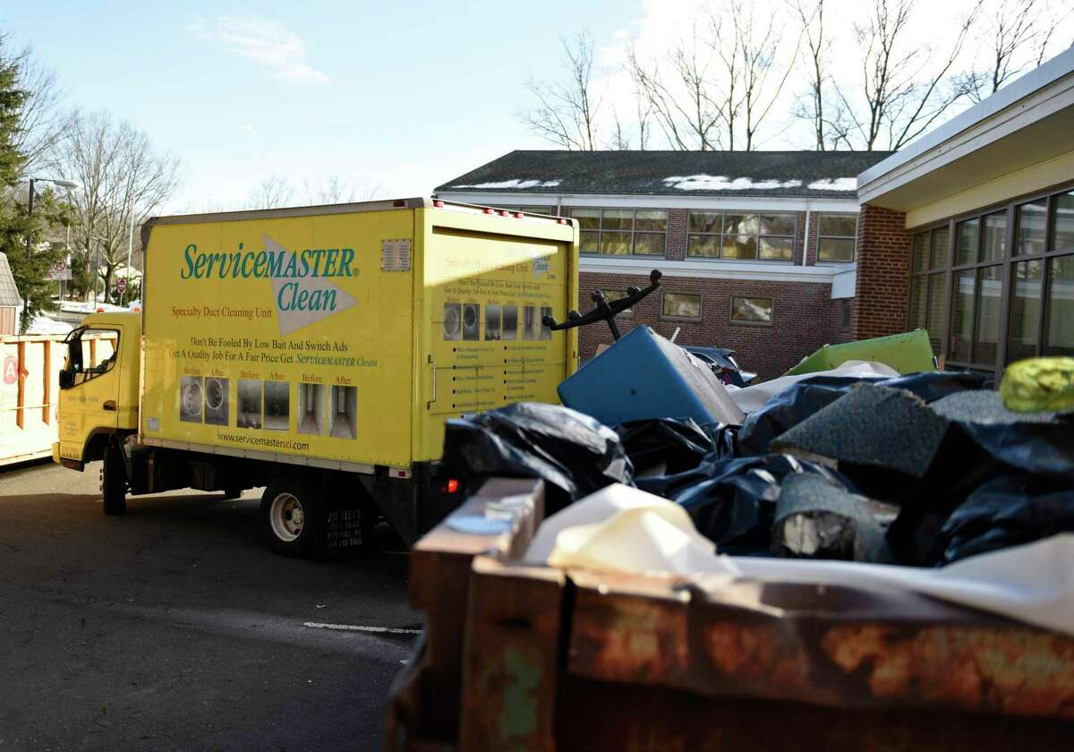 An HVAC truck pulls away as damaged items are piled into a dumpster outside North Mianus School in the Riverside section of Greenwich, Conn. Tuesday, Feb. 16, 2021. The school flooded the weekend before, causing extensive damage.