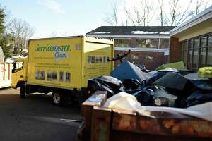 An HVAC truck pulls away as damaged items are piled into a dumpster outside North Mianus School in the Riverside section of Greenwich, Conn. Tuesday, Feb. 16, 2021.
