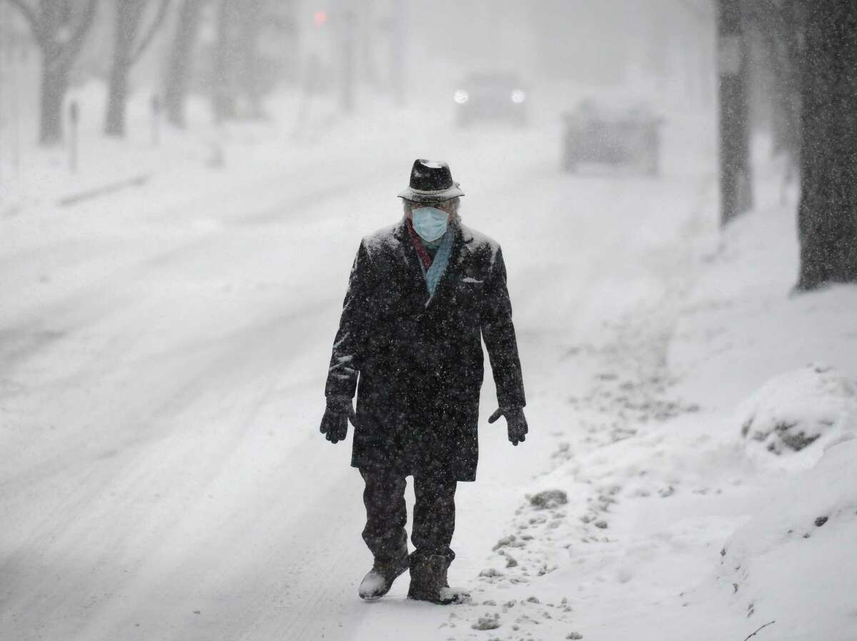 A man trudges through the snow along Mason Street in Greenwich, Conn. Thursday, Feb. 18, 2021. The area received a blanketing of snow starting Thursday morning that is expected to last into Friday.