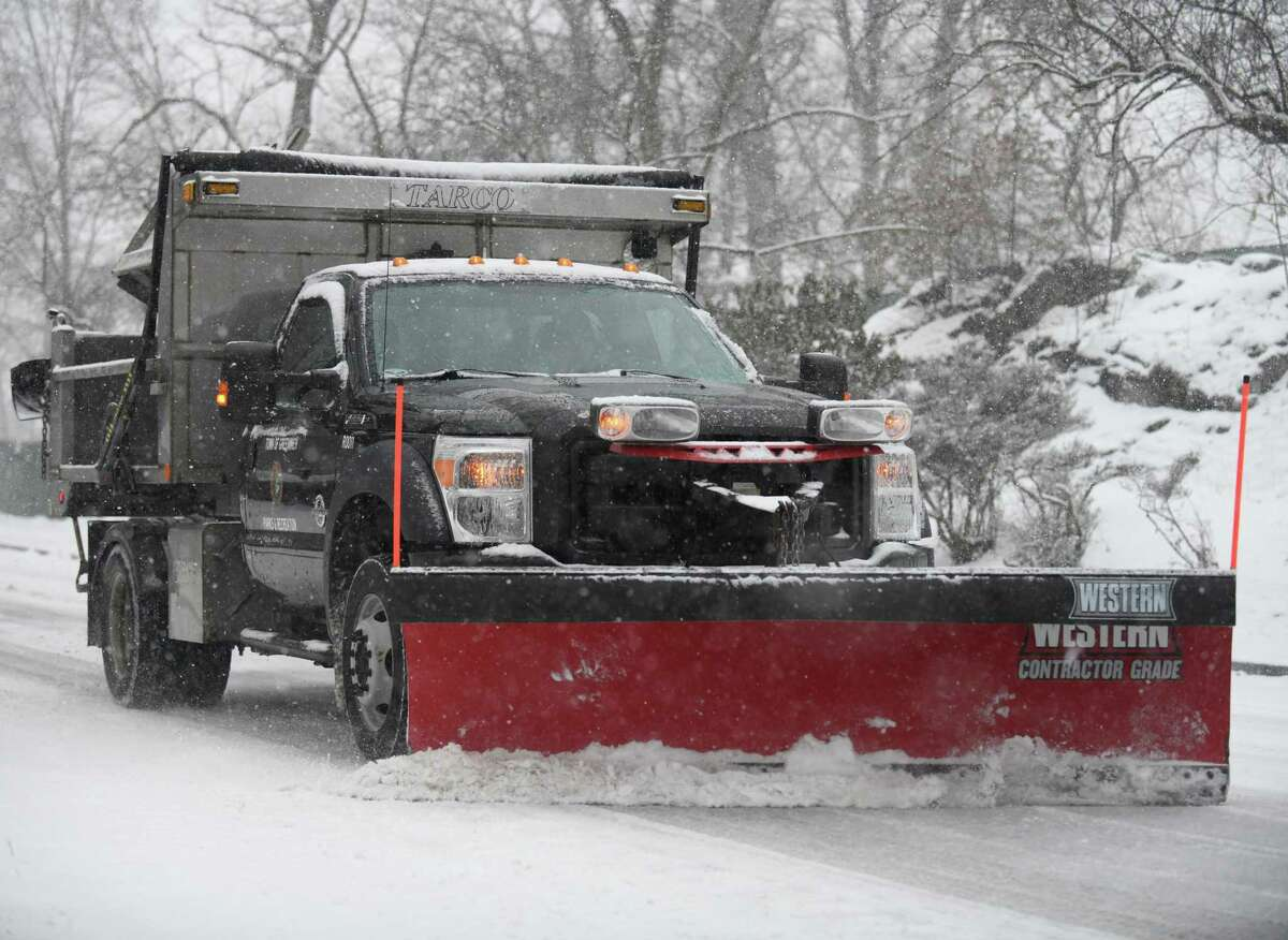 A plow clears snow near the Bruce Museum in Greenwich, Conn. Thursday, Feb. 18, 2021. The area received a blanketing of snow starting Thursday morning that is expected to last into Friday.