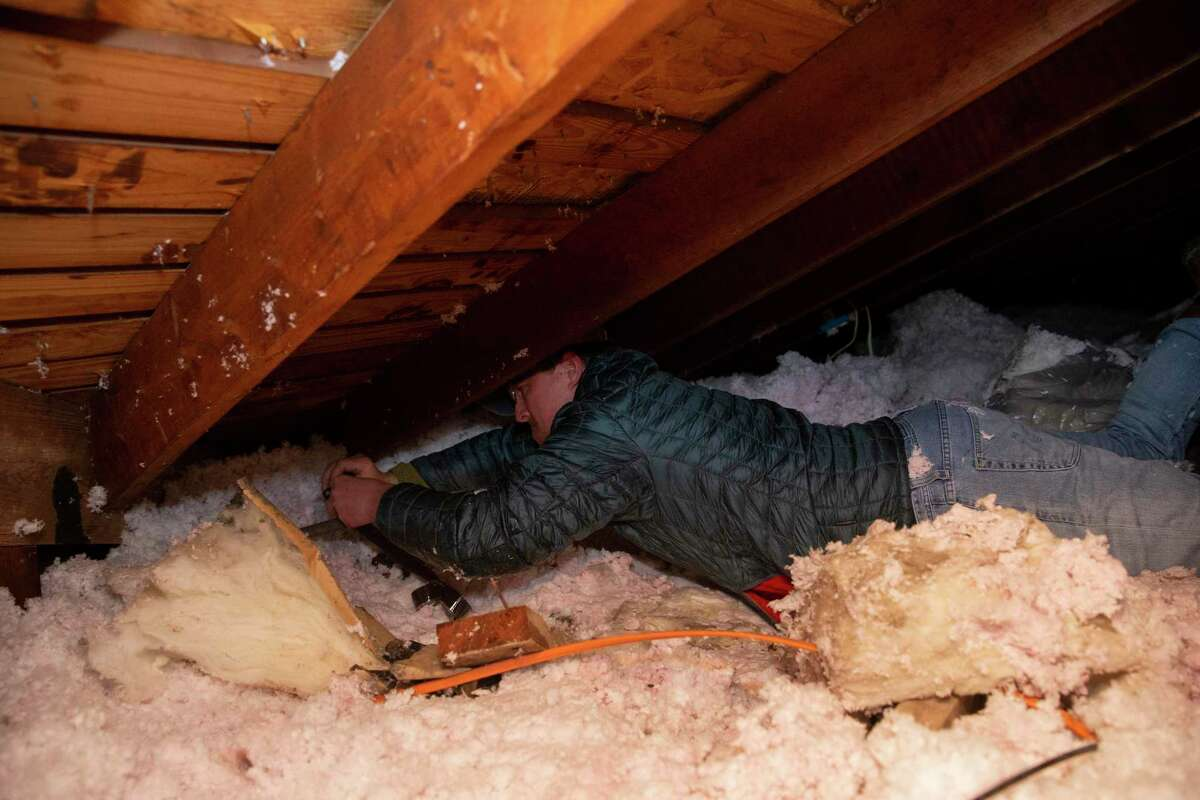 Nick Conway crawls into his attic and fixes a burst water pipe, due to the cold weather, with a repair tape Wednesday, Feb. 17, 2021, in Houston. Conway called his plumber but was told he was the 10th person on the line so he purchased the tape to fix the pipe himself.