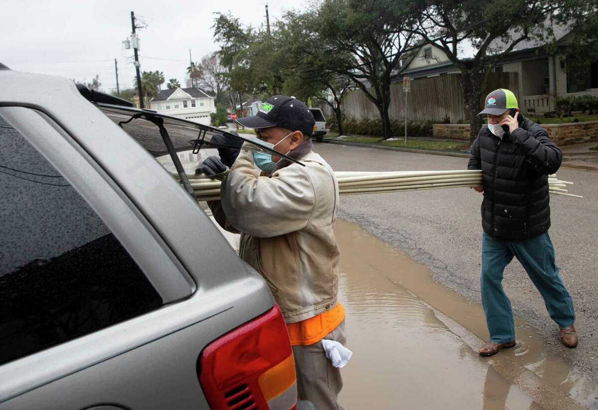 Worldwide Contracting & Roofing contractors Agustin Ramirez, left, and Javier Espinoza load pipes they bought at U-Plumb-It to fix burst pipes for their customers Wednesday, Feb. 17, 2021, in Houston.