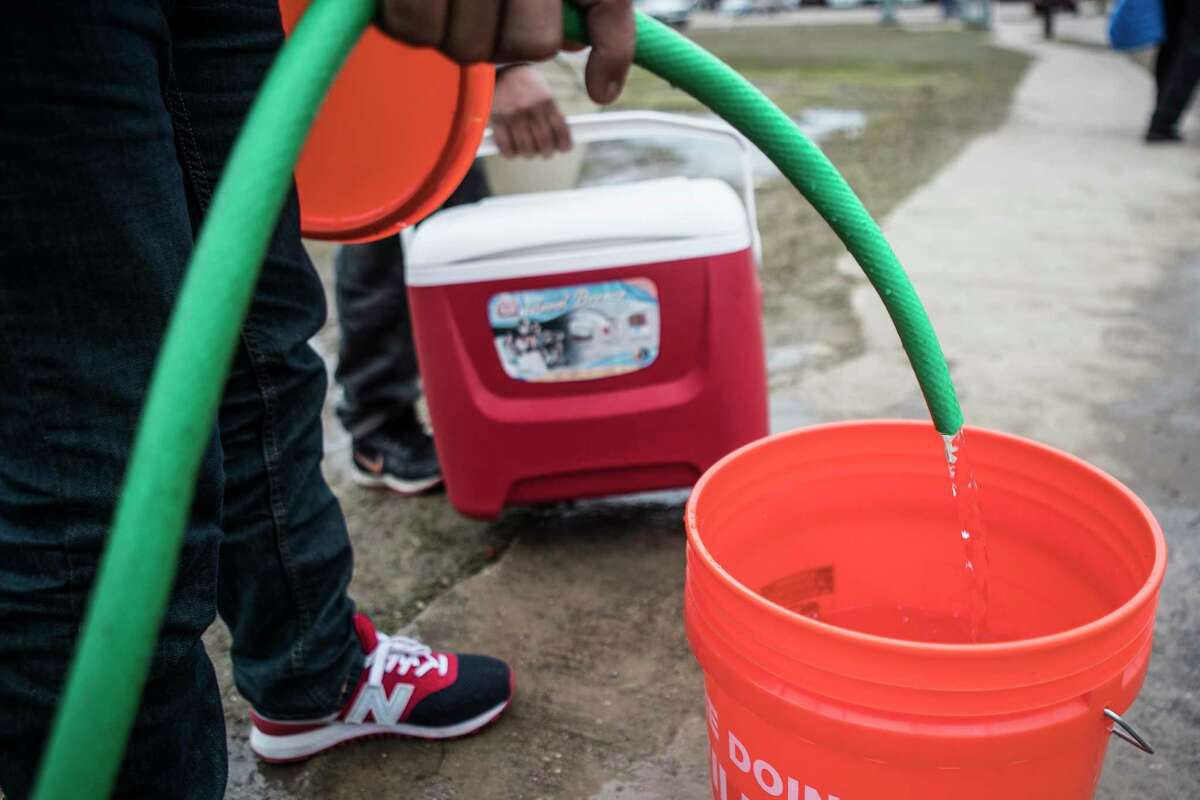 People fill containers of various sizes from a spigot at Haden Park Thursday, Feb. 18, 2021 in Houston. Houston and several surrounding communities were under a boil water notice as many residents are still without running water in their homes, despite power returning to the region.