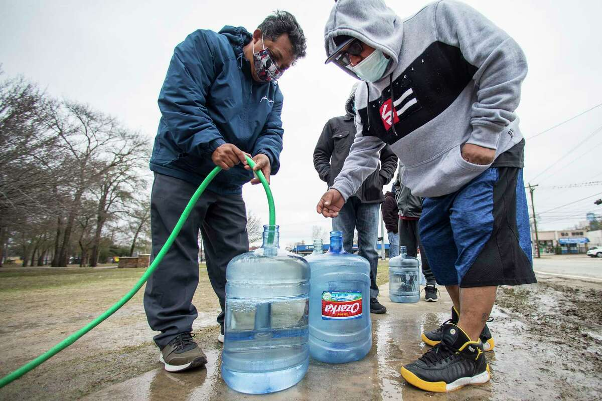 Victor Hernandez, left, and Luis Martinez fill their water containers with a hose from a spigot in Haden Park as others wait in near freezing temperatures Thursday, Feb. 18, 2021 in Houston. Houston and several surrounding communities are under a boil water notice as many residents are still without running water in their homes, despite power returning to the region.