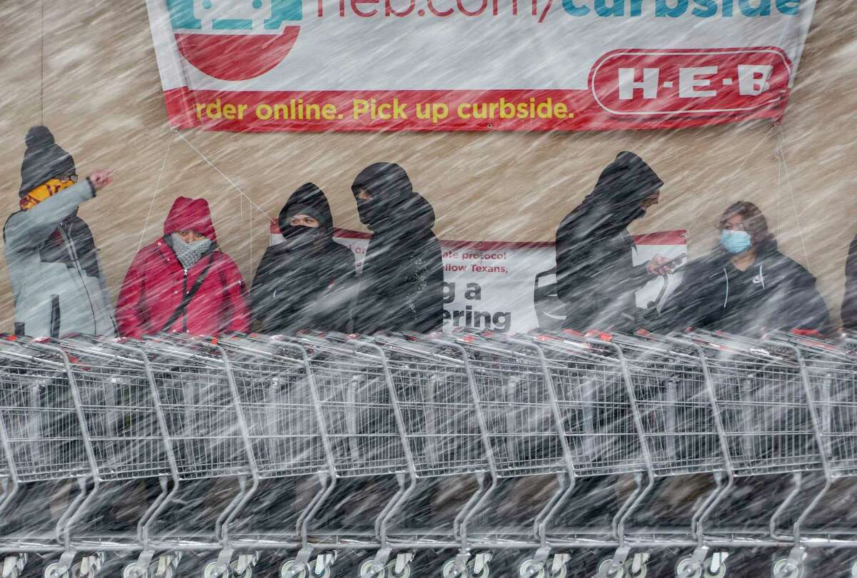 People wait in line to enter the H-E-B at West Avenue and Blanco Road as a brisk snow falls on Thursday morning, Feb. 18, 2021.