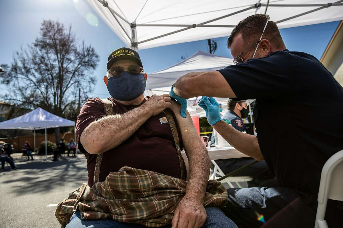 Rocky Morton, 73, receives a Moderna COVID-19 vaccine from fire engineer - EMT Cliff Colyer during a pop-up vaccination clinic at the Gilroy Senior Center onFeb. 17, 2021.