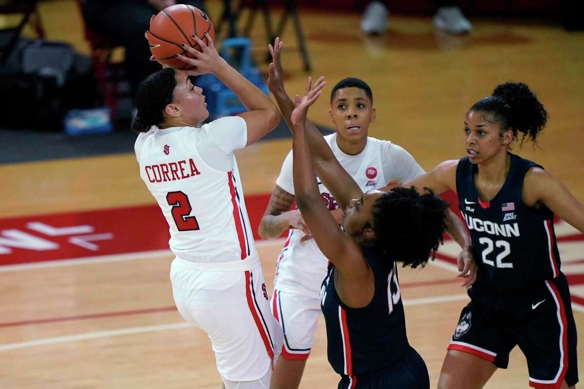 St. John's guard Leilani Correa (2) shoots while defended by UConn's guard Christyn Williams (13) on Wednesday in New York.