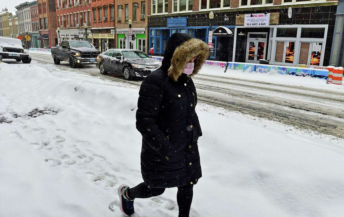A pedestrian makes their way down Washington Street as they deal with the first wave of snow Thursday, February 18, 2021, in Norwalk, Conn.