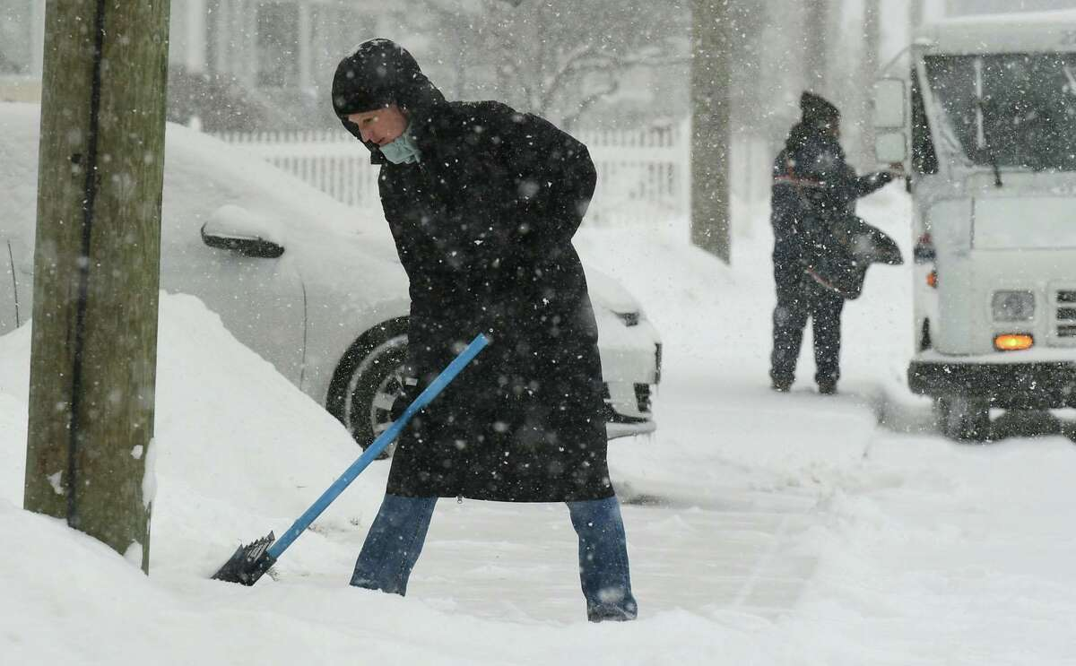 A resident of Edlie Avenue clears the first wave of snow Thursday, February 18, 2021, in Norwalk, Conn.