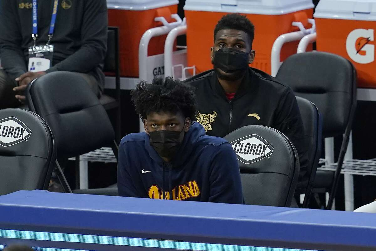 Injured Golden State Warriors centers James Wiseman, left, and Kevon Looney watch against the Orlando Magic during an NBA basketball game in San Francisco, Thursday, Feb. 11, 2021. (AP Photo/Jeff Chiu)