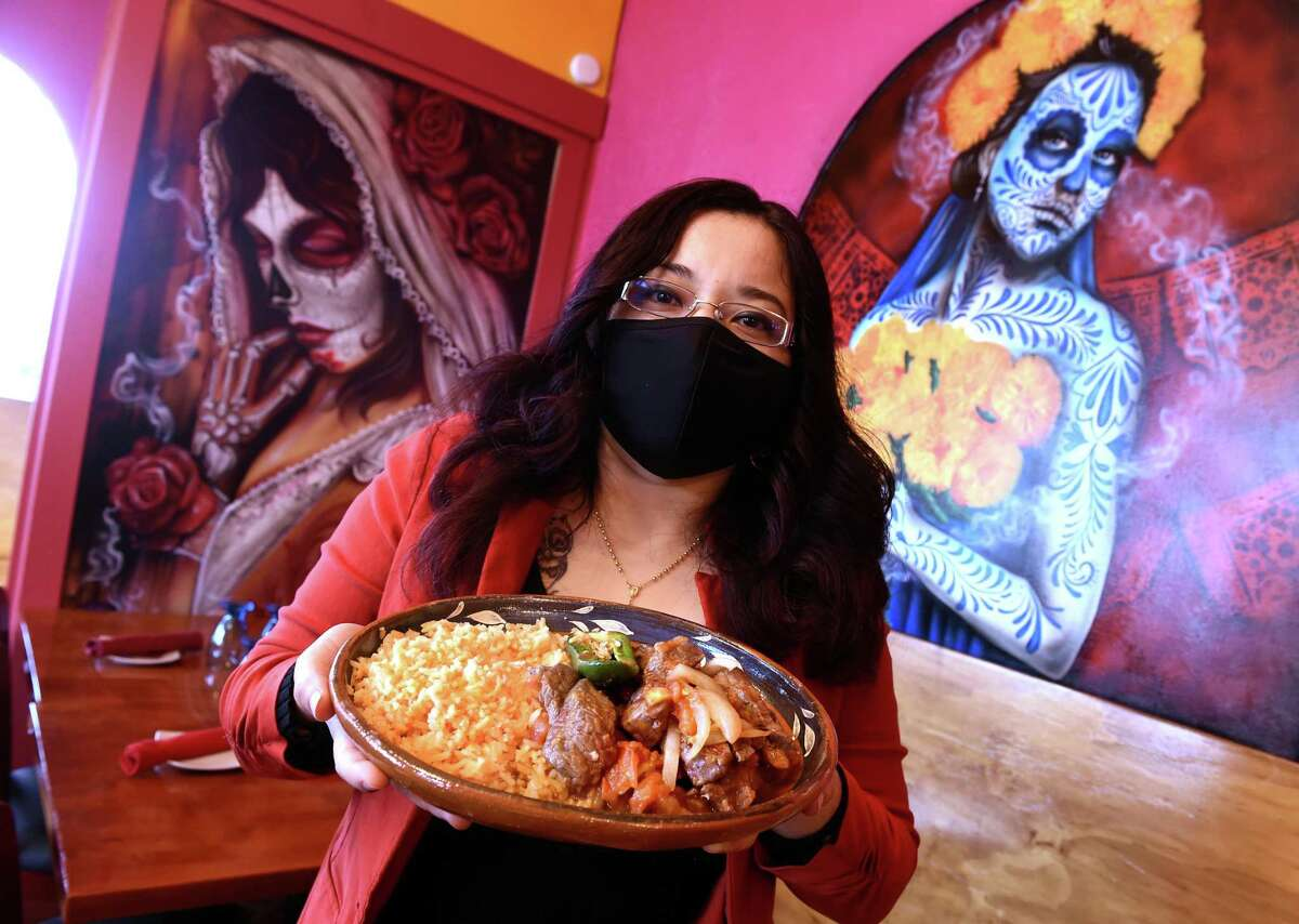 Karen Sanchez Benitez, one of four owners of La Catrina, holds Bistec a la Mexicana at the West Haven Mexican restaurant on February 16, 2021. In the background are murals painted by Cruz Manuel.