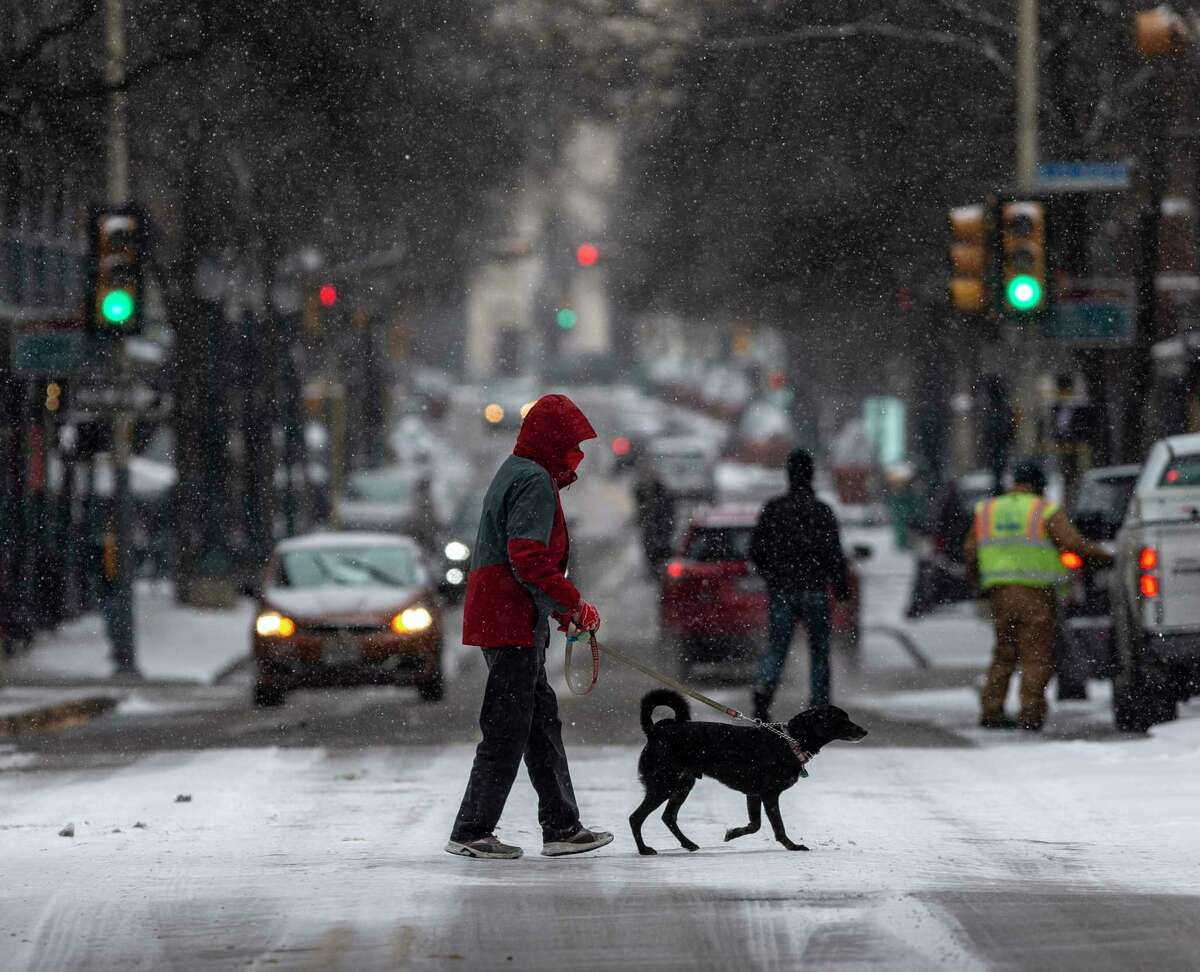 A person and their dog cross Houston Street Thursday, Feb. 18, 2021 as snow grips the city for the second time in a week, the result of an arctic air mass that sent temperatures plummeting and resulted in rolling blackouts across the city and the state. At one point about 1/3 of all CPS Energy customers were without electricity.