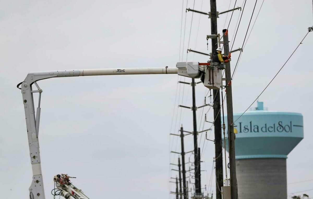 A utility worker works on a power line on Galveston Island on Thursday, Feb. 18, 2021.