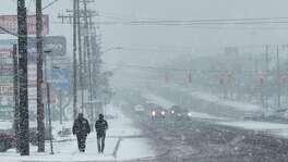 People walk along Blanco Road as a brisk snow falls on Thursday morning.