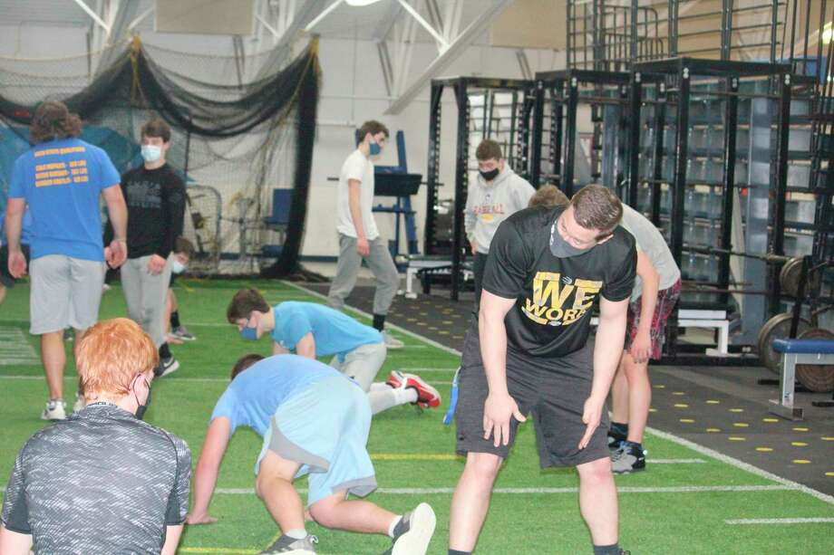 Evart wrestling coach Ben Bryant (right) supervises a preseason conditioning session in the Wildcat weight room. (Pioneer file photo)