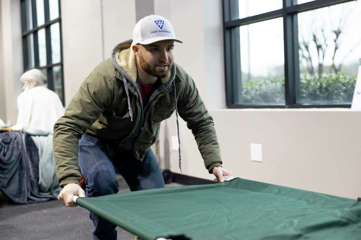 Jonathan Collins with the Church Project prepares a cot, Thursday, Feb. 18, 2021, in The Woodlands. People as far as Friendswood were transported to the warming center due to outages in their area and hotels being at max capacity.