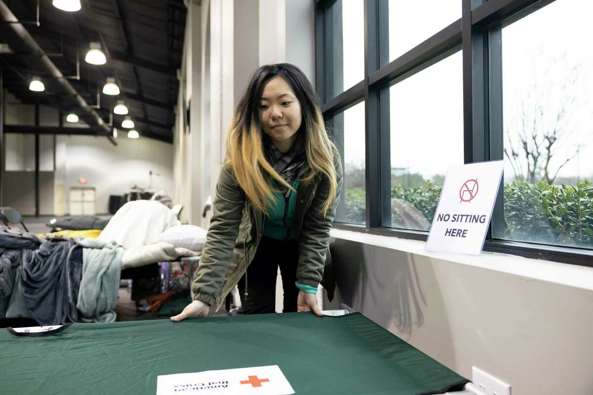 Tammy Lee with the Church Project prepares a cot, Thursday, Feb. 18, 2021, in The Woodlands. People as far as Friendswood were transported to the warming center due to outages in their area and hotels being at max capacity.