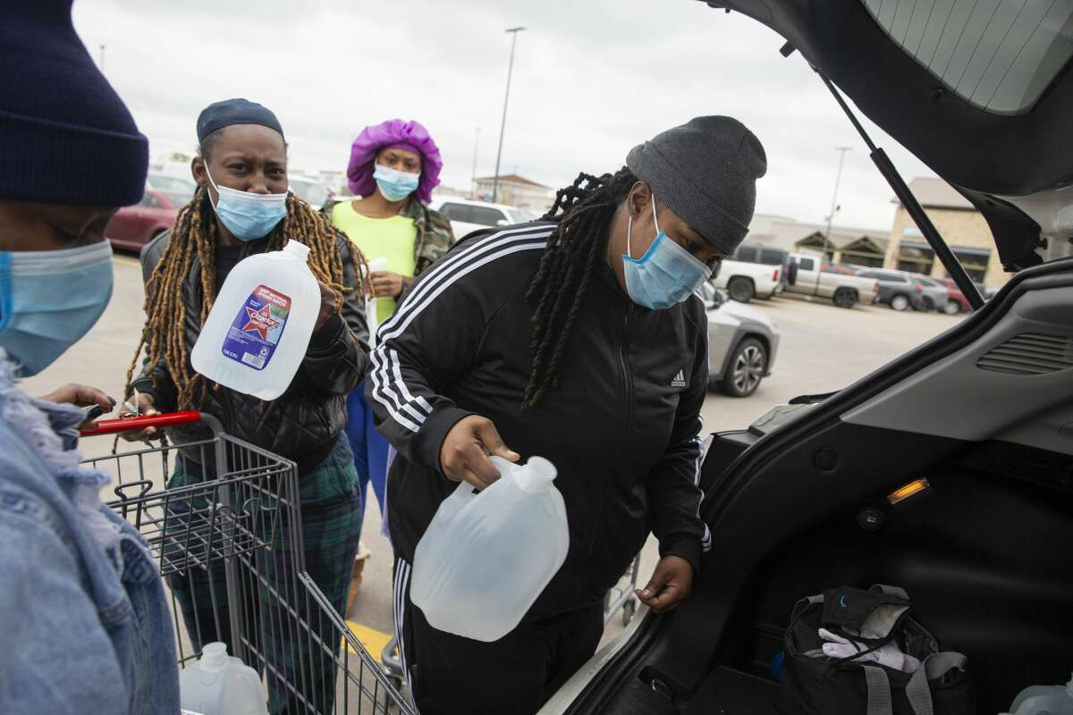 Nycole Fields, from front left, and fiancee Kortney Fields, Destiny Hudson and wife Keisha Hudson putting water they purchased at a grocery into the trunk Thursday, Feb. 18, 2021, in Houston.