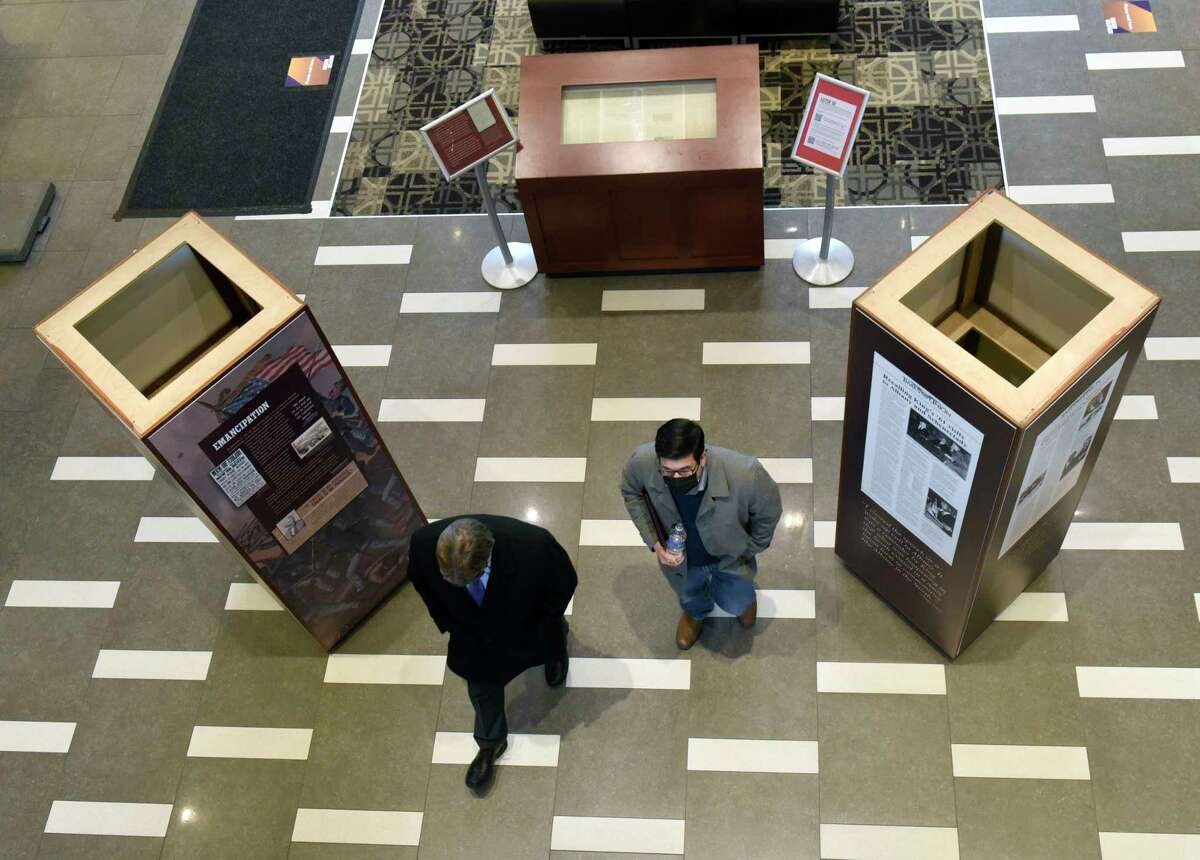 People walk away after looking at President Abraham Lincoln's only surviving handwritten preliminary version of the Emancipation Proclamation which is part of the First Step to Freedom exhibit at University at Albany on Thursday, Feb. 18, 2021 in Albany, N.Y. (Lori Van Buren/Times Union)