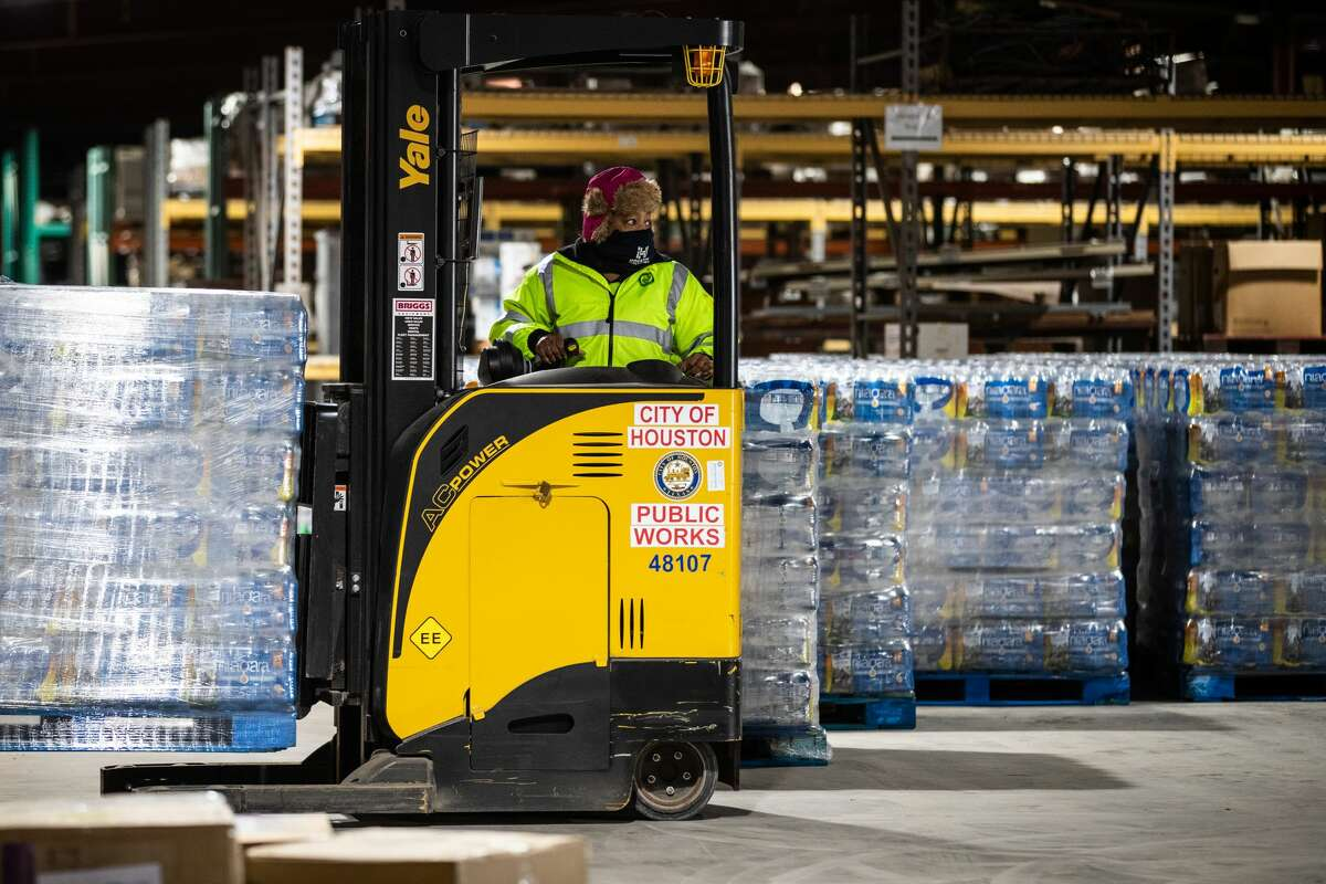 A worker transports bottles of water from the City of Houston Upper Braes Warehouse to delivery trucks, Thursday, Feb. 18, 2021, in Houston. Houston is currently under a boil water notice because of issues with the water treatment process due to the cold weather.
