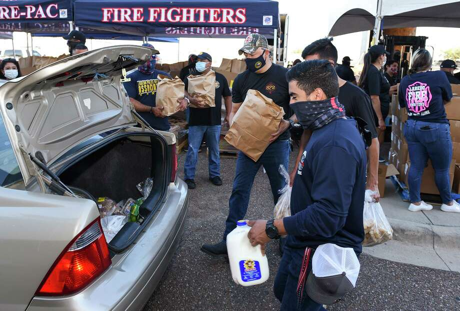 Members of the Laredo Fire-Pac volunteer to help distribute food, Friday, Jun 12, 2020, during the Laredo Regional Food Bank's Food Drive at the UISD Student Activity Complex. Photo: Danny Zaragoza, Staff Photographer / Laredo Morning Times