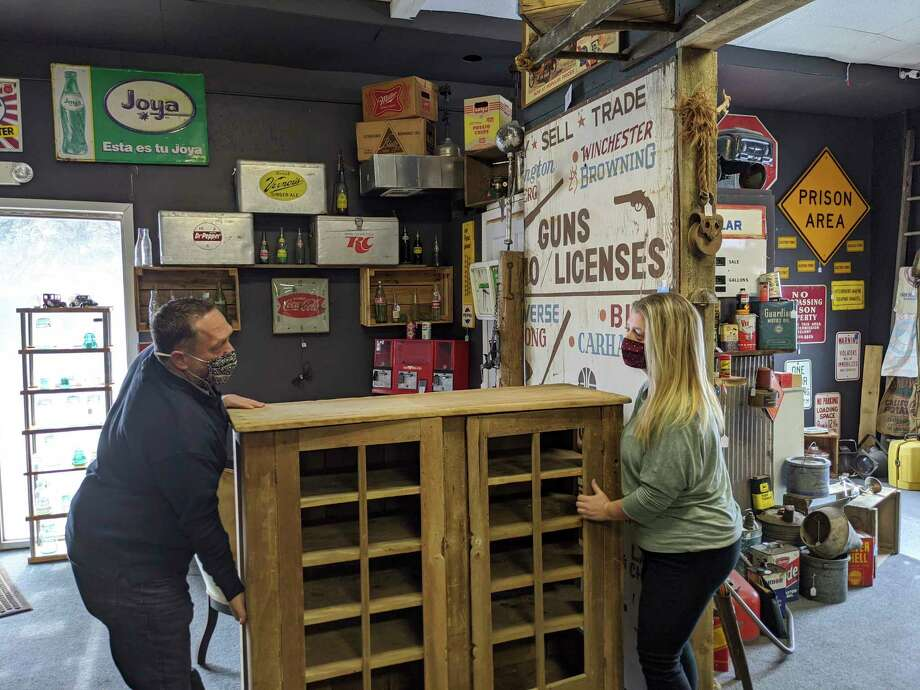 Beaverton Antique Mall vendor, Stan Lenneman, left, and owner Melissa Frye move a recently purchased pie safe. (Photo by Tereasa Nims, For the Daily News)