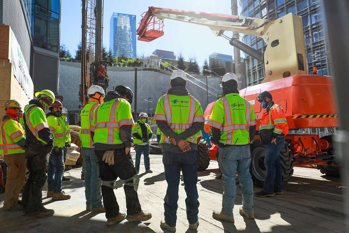 Construction crews gather for a meeting as they work at Millennium Tower on Mission Street.