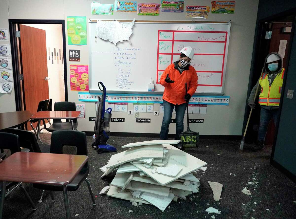Workers clean up damage in a classroom from broken water pipes in the fire suppression system at Tomball Memorial High School Thursday, Feb. 18, 2021 in Tomball.