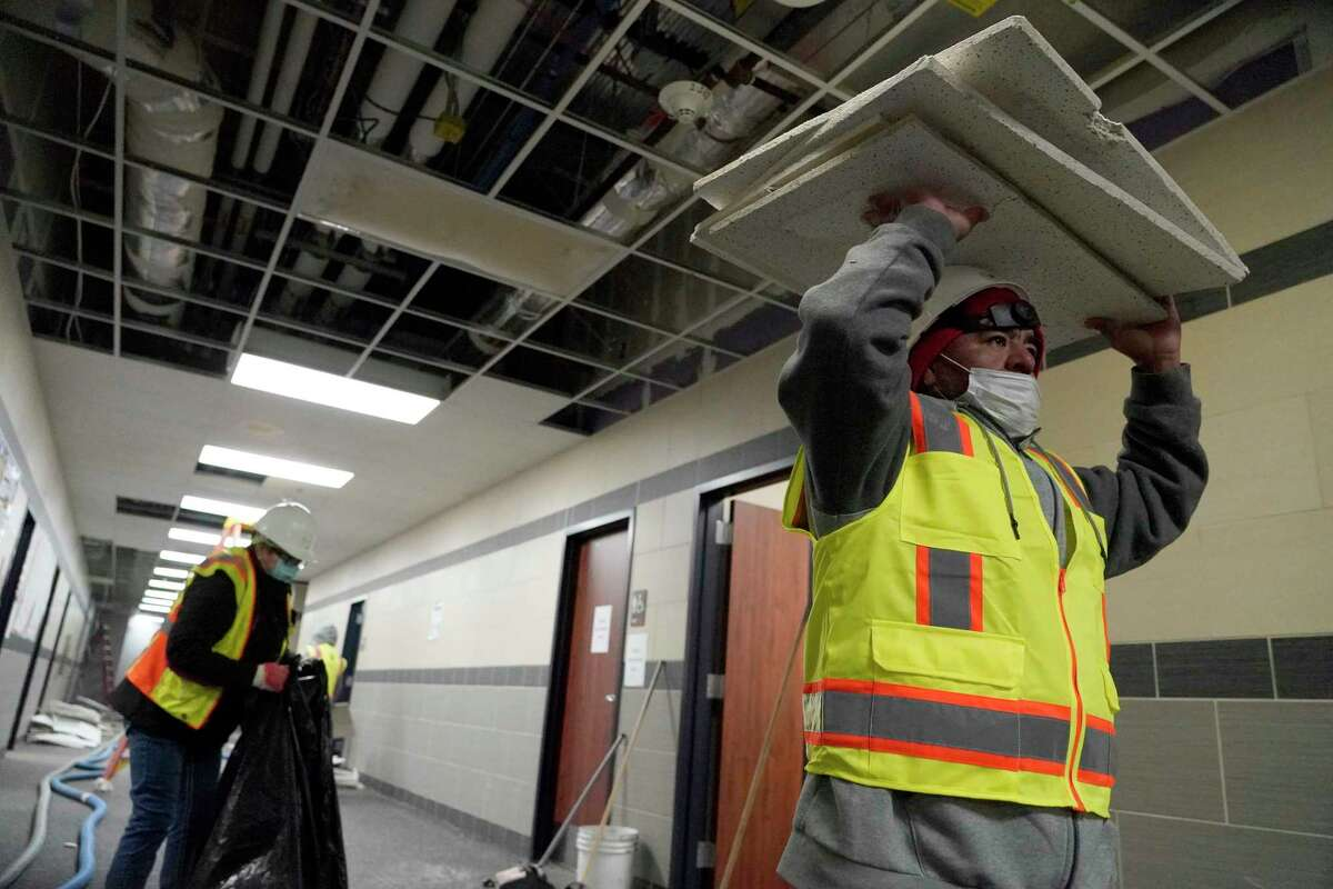 Workers clean up damage from broken water pipes in the fire suppression system at Tomball Memorial High School Thursday, Feb. 18, 2021 in Tomball.