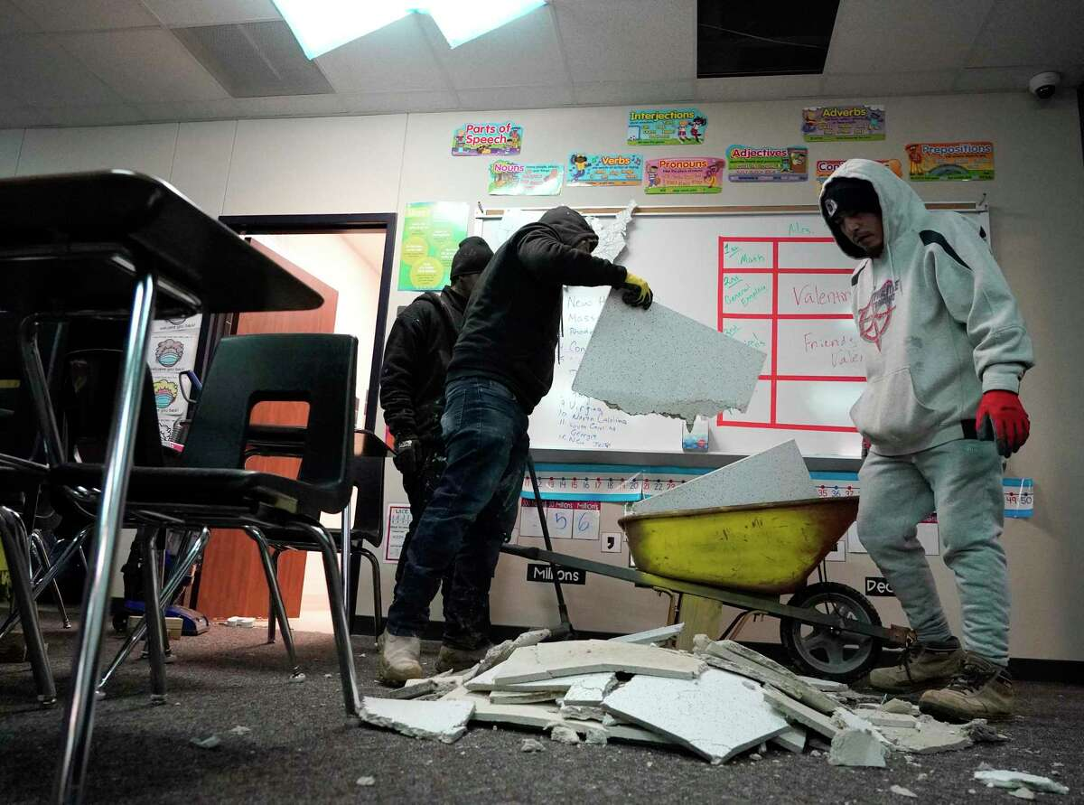 Workers clean up damage Thursday in a classroom caused by broken pipes in the fire suppression system at Tomball Memorial High School.