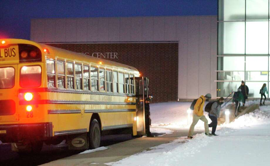 Students step off the bus and head to class at Manistee Middle High School. (File photo)