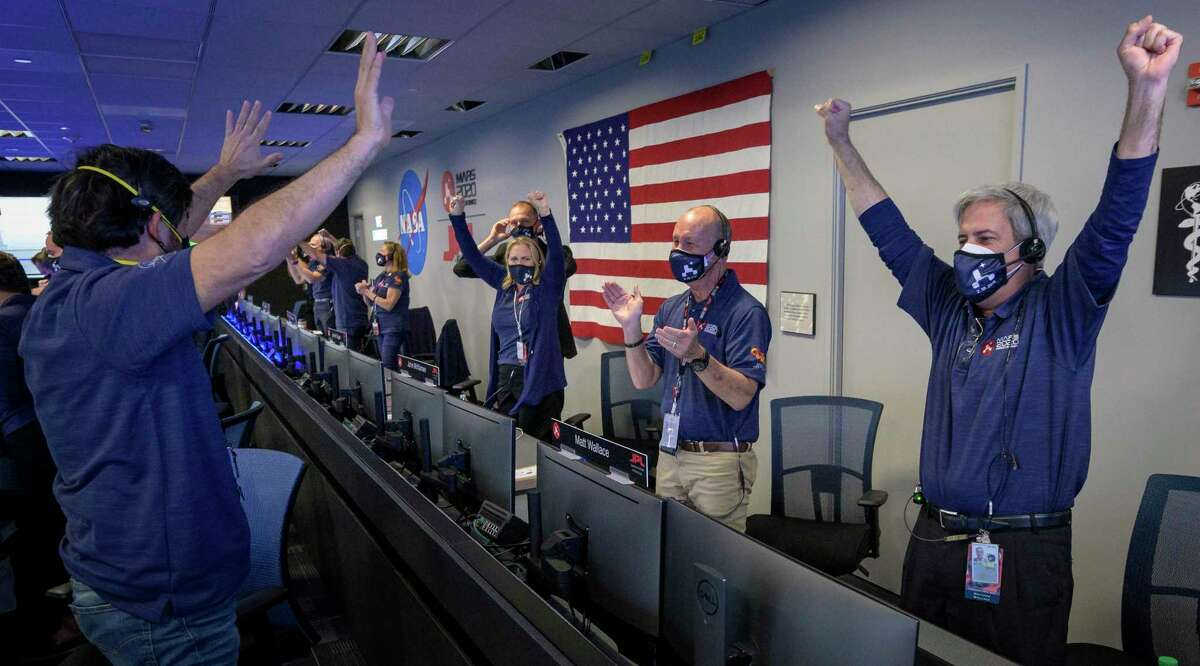 A photo provided by NASA, shows members of NASA's Perseverance rover team reacting in mission control after receiving confirmation the spacecraft successfully touched down on Mars, Thursday, Feb. 18, 2021, at NASA's Jet Propulsion Laboratory in Pasadena, Calif. (Bill Ingalls/NASA via The New York Times)