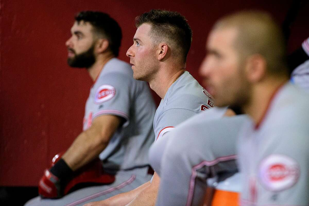 PHOENIX, ARIZONA - SEPTEMBER 14: Anthony DeSclafani #28 of the Cincinnati Reds sits in between Jose Peraza #9 (L) and Joey Votto #19 (R) during the MLB game against the Arizona Diamondbacks at Chase Field on September 14, 2019 in Phoenix, Arizona. (Photo by Jennifer Stewart/Getty Images)